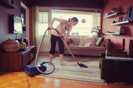 Woman is vacuum cleaning living room carpet on an apartment building