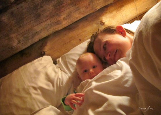 Baby and mother in bed in cottage