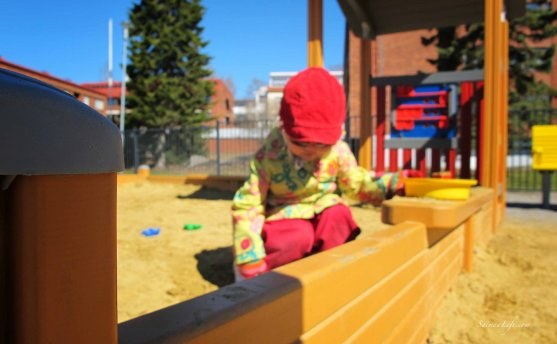 young girl playing in sand box