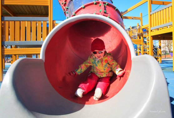 girl sliding through tube playground