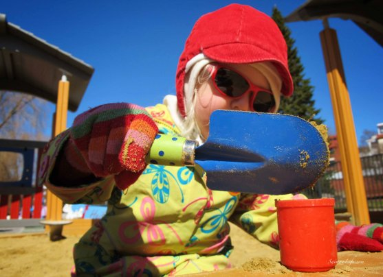 girl making sandcakes at the playground