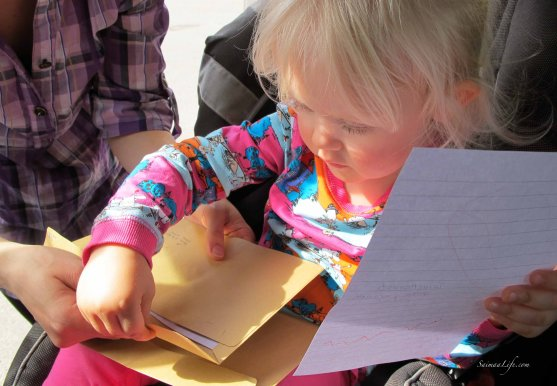 child-putting-drawing-to-envelope