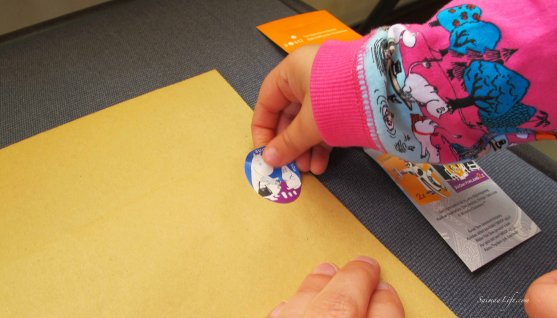 child-putting-moomin-stamp