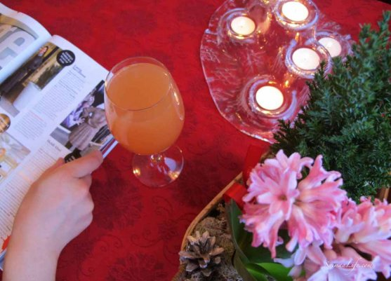 woman reading a women's magazine and having a glass of apple juice with candles on the table with some flowers