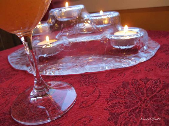 a wine glass on the table and small candles burning in the background