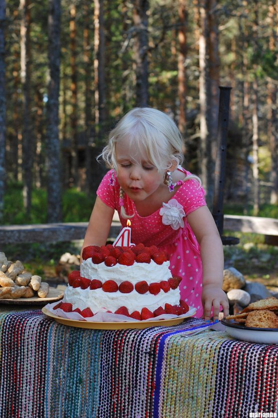 child-blowing-candles-from-her-strawberry-cake-in-summer