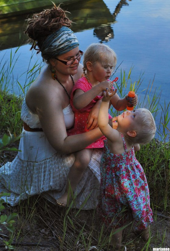 child-blowing-soap-bubbles-with-her-godparent