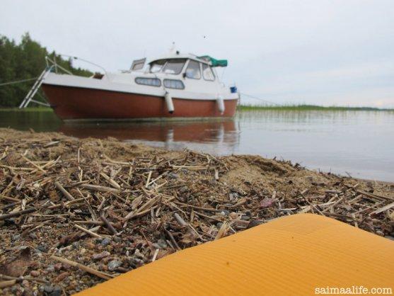 practising-yoga-by-lake-next-to-boat