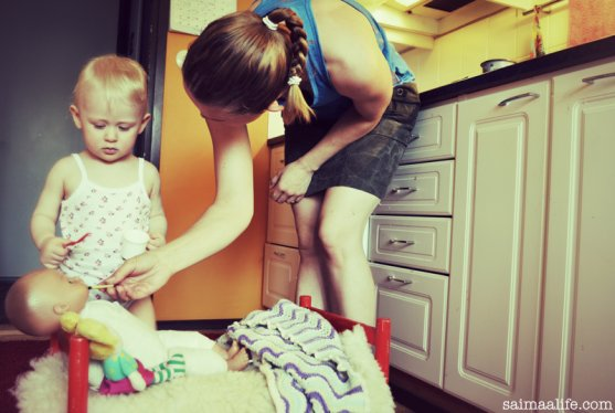 working-mom-cooking-and-playing-with-child-at-the-same-time