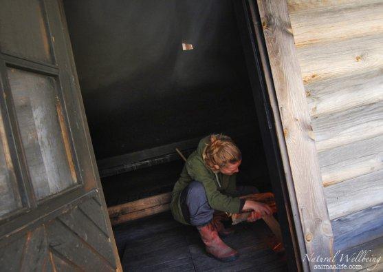 woman-adding-wood-to-finnish-smoke-sauna