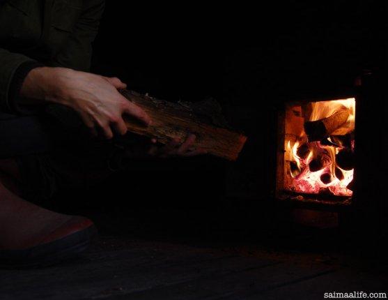 woman-adding-wood-to-sauna