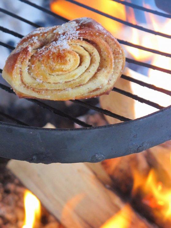 cinnamon-roll-warming-up-on-fireplace