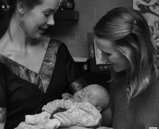 Two women holding a baby girl