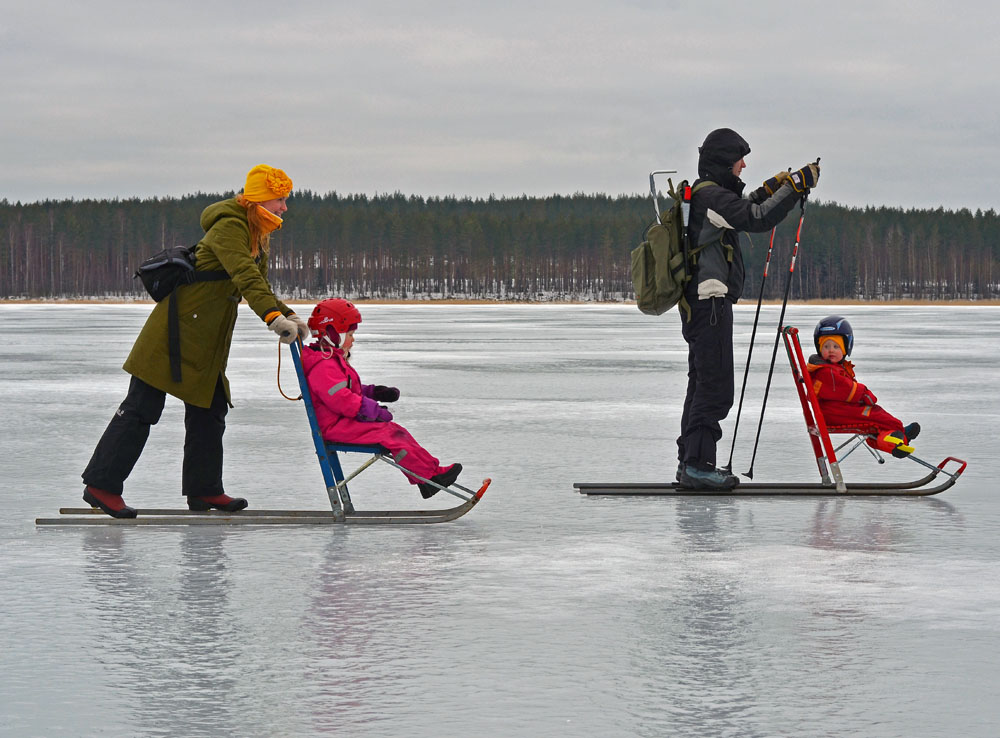 family-kick-sledding-on-lake
