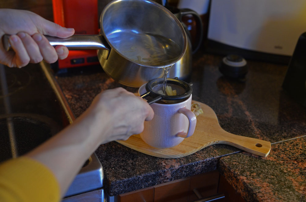 filtering homemade ginger tea for pain relief