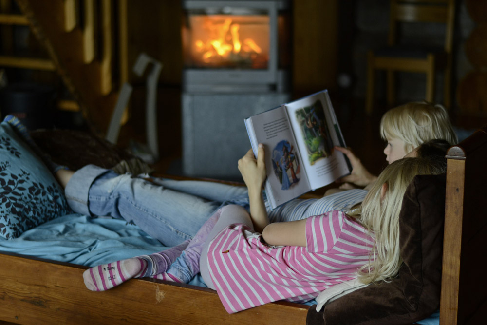 mother-reading-children-book-by-the-fireplace