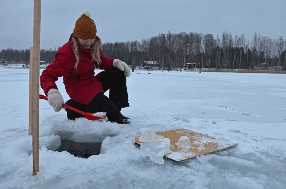 Making a hole in the ice before winter fishing - SaimaaLife.com
