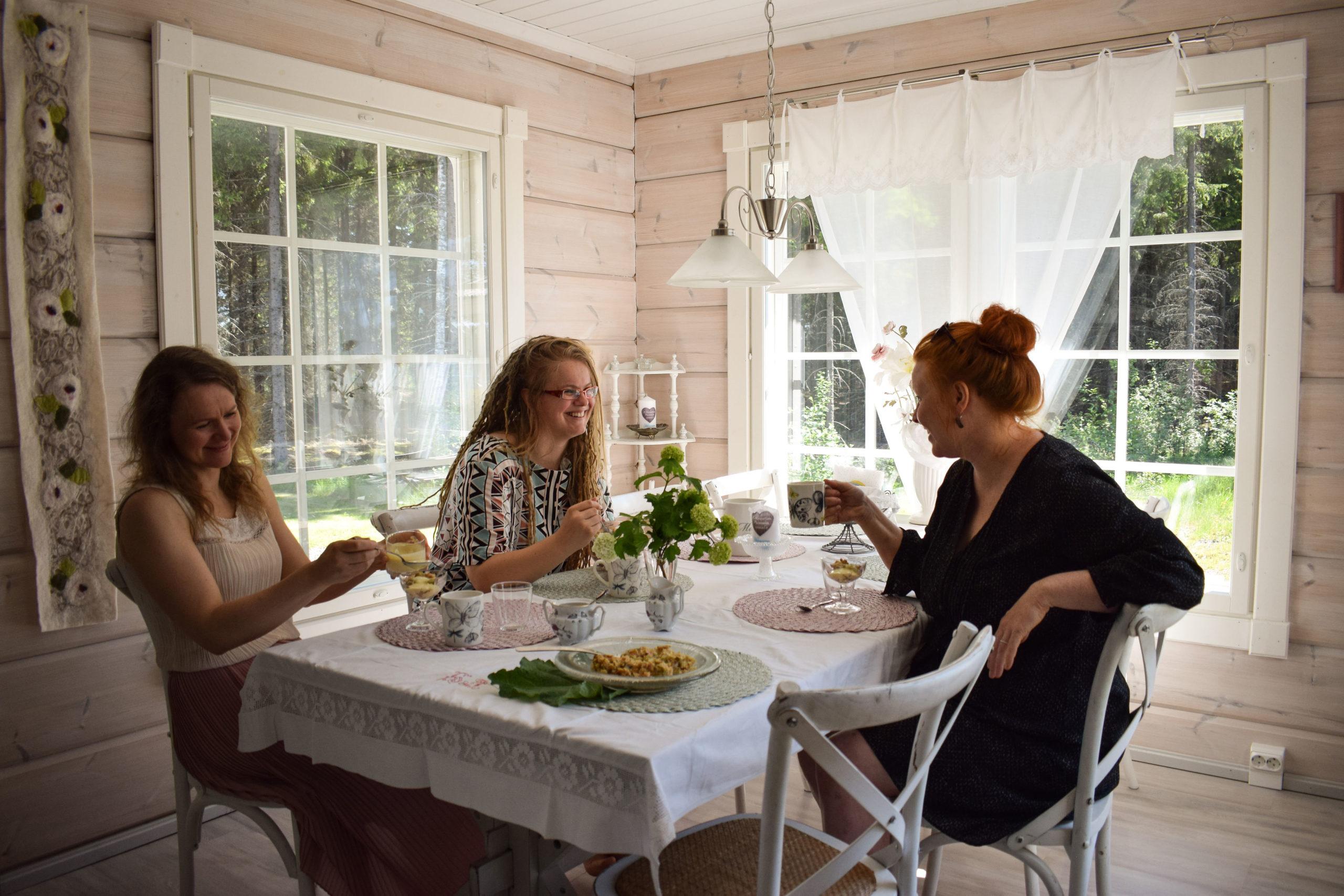three women sitting at the table in lakeside cottage of hienosen lomamökit