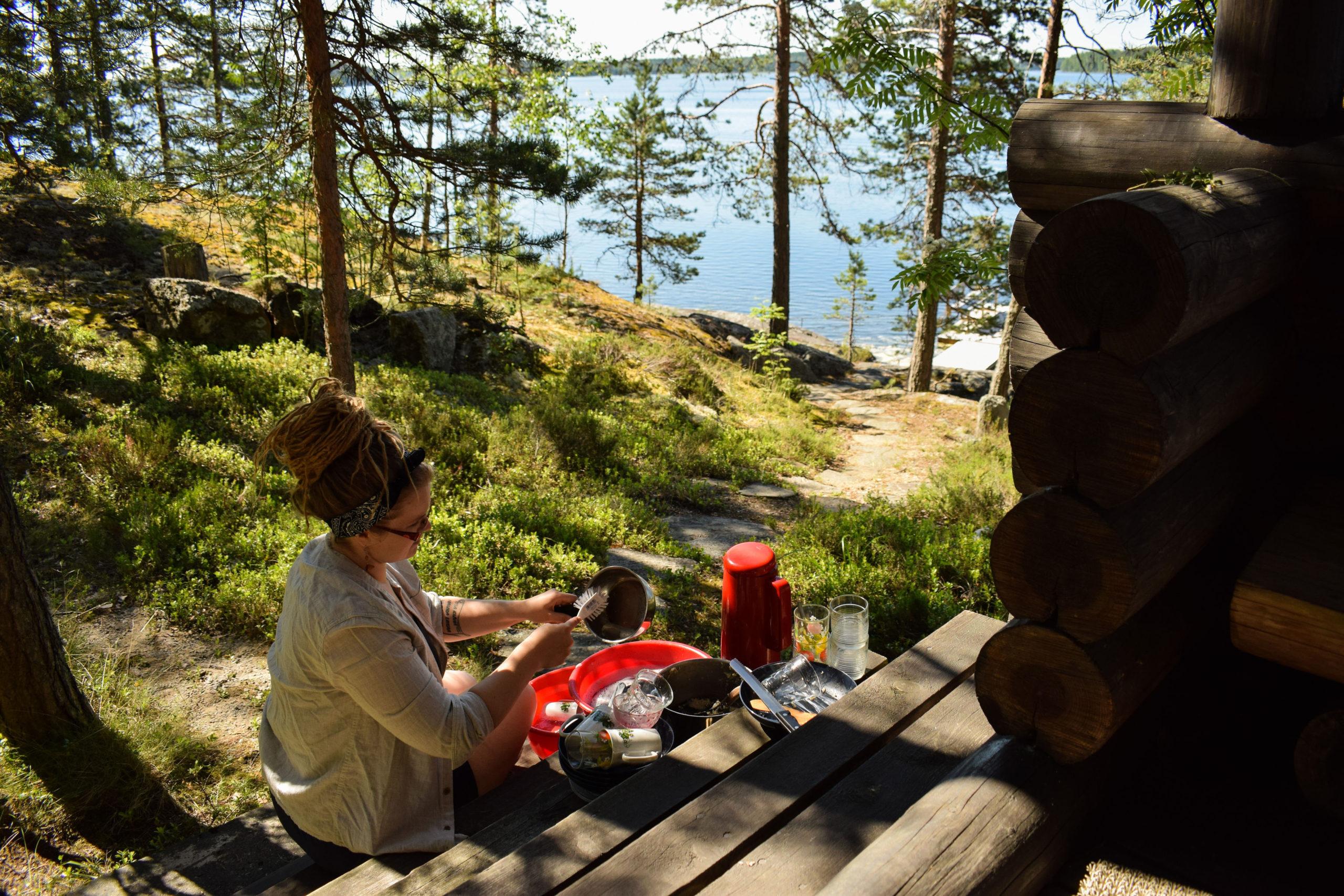 Woman doing dishes outdoors at Kukkoniemen Lomamökit rental cottages in Punkaharju, Saimaa