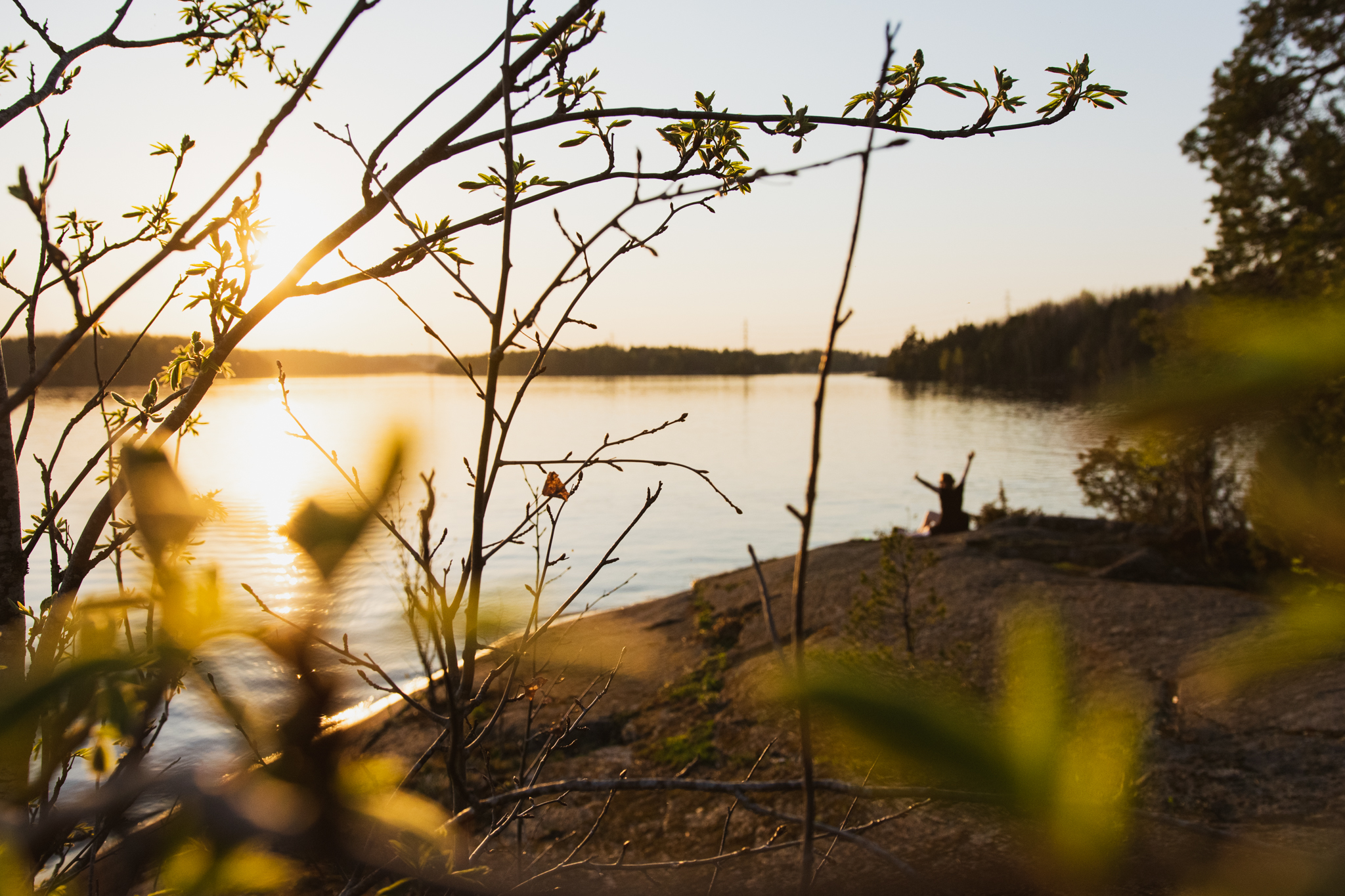 Woman sitting by the lake in spring and watching the sunset in Saimaa, Finland