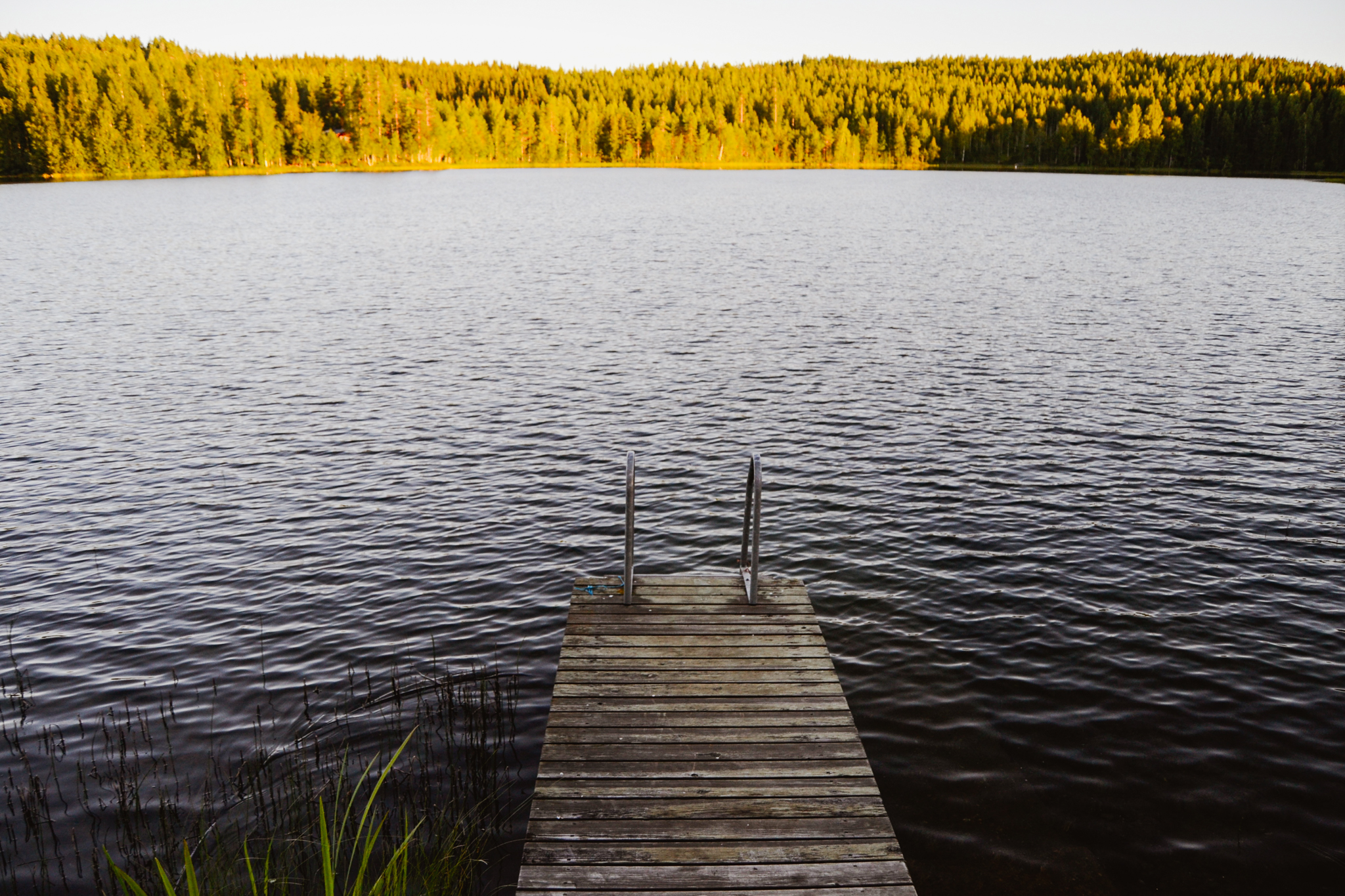 dock by the Finnish lake on calm summer evening