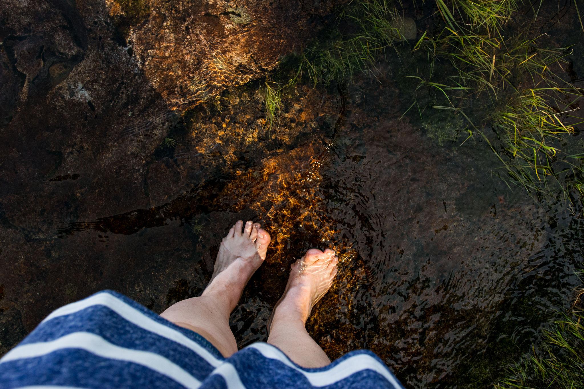 finnish woman relaxing barefoot on clear saimaa lake water