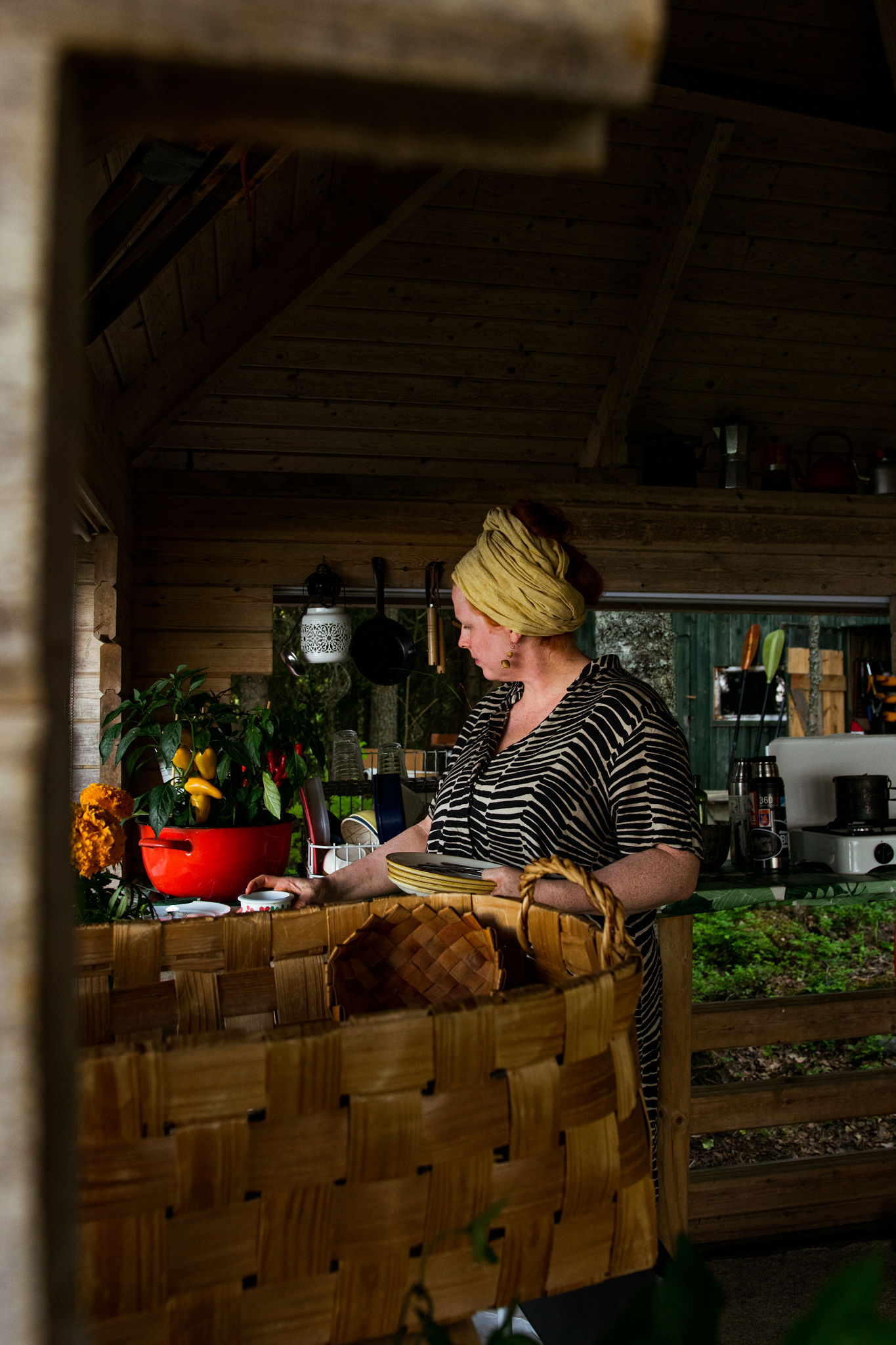 woman preparing grilling food in outdoor kitchen at summer cottage in saimaa